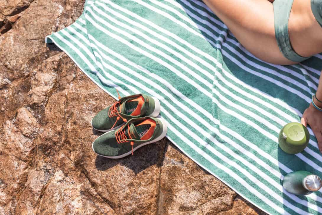 Girls lays on towel next to quick dry travel shoes