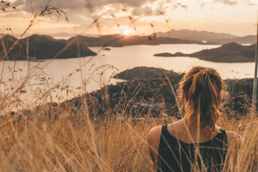 Girl watching sunset over islands in the Philippines