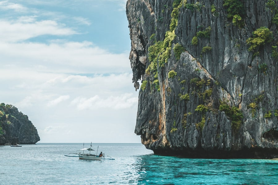 Small boat beside limestone karst in El Nido, The Philippines.