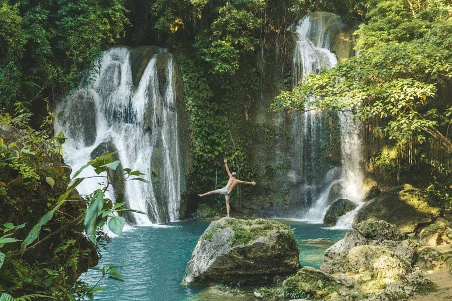 Man stands in front of two waterfalls in Bohol
