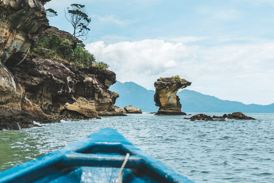 Views of rock formations in Bako National park from a blue boat.