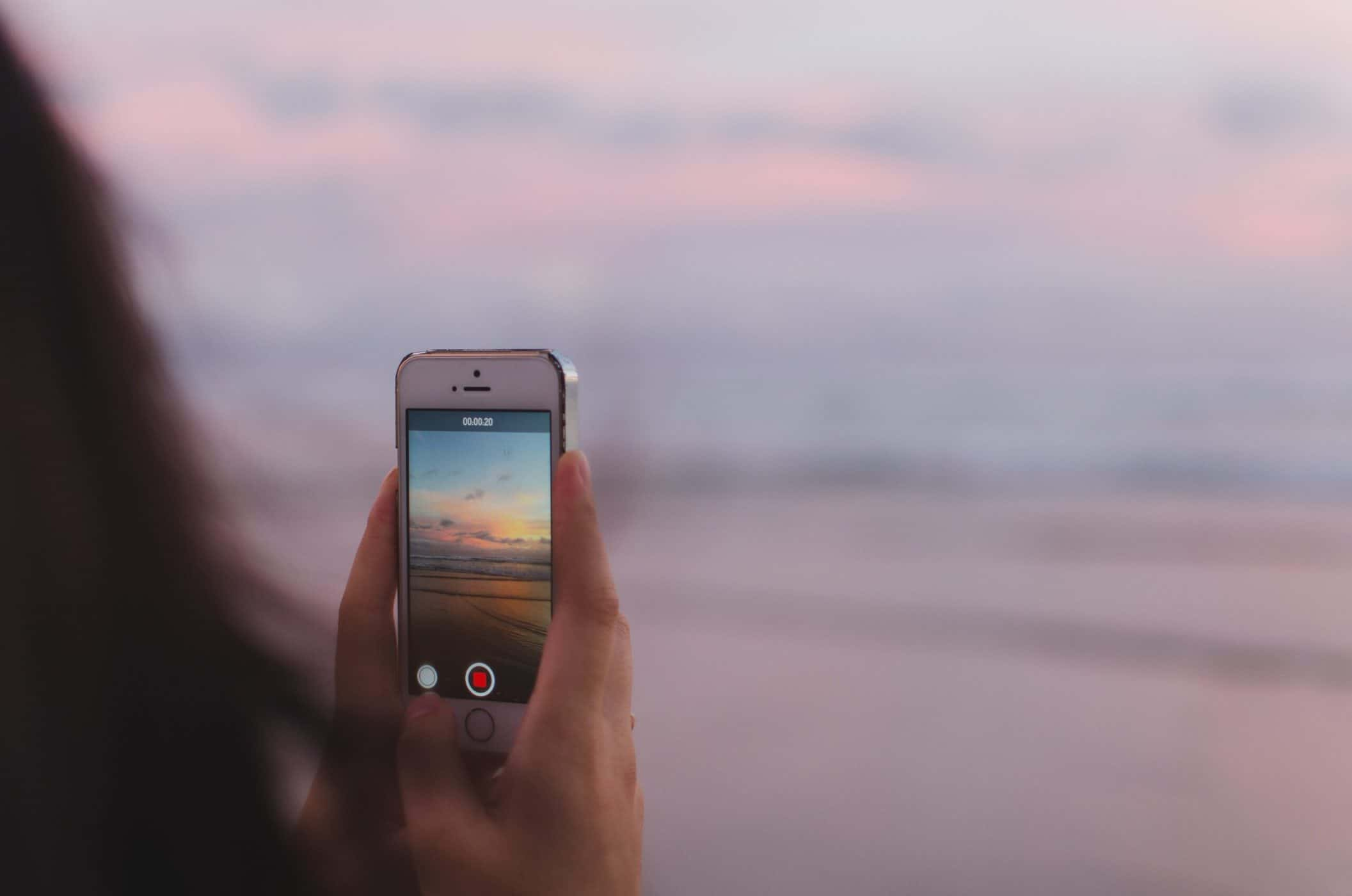 Videoing sunset and sea on mobile phone.