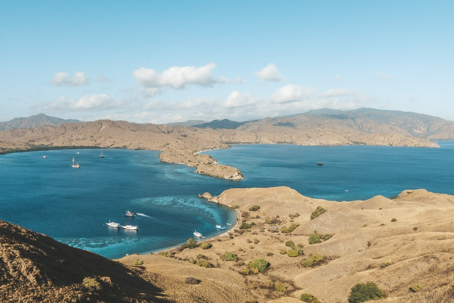 View of an interestingly shaped island and boats in the lagoon in Komodo National Park.