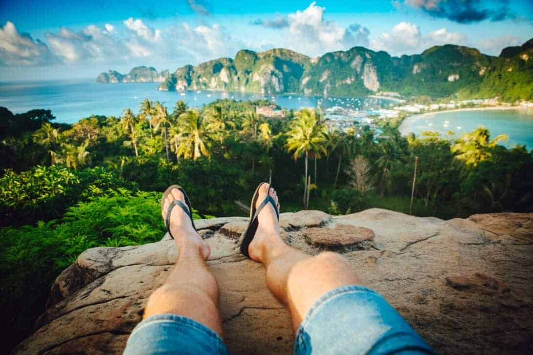 A man with flip flops sits on the cliff in Koh Phi Phi, Thailand.