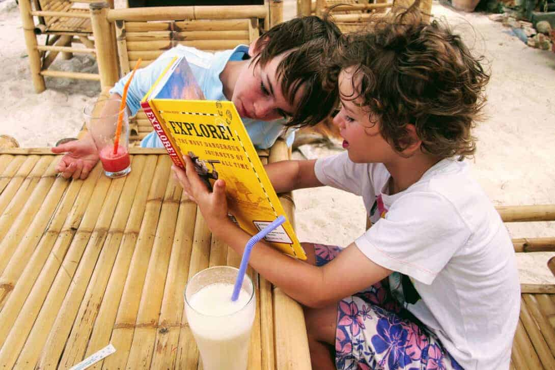 Kids reading books while travelling in Thailand