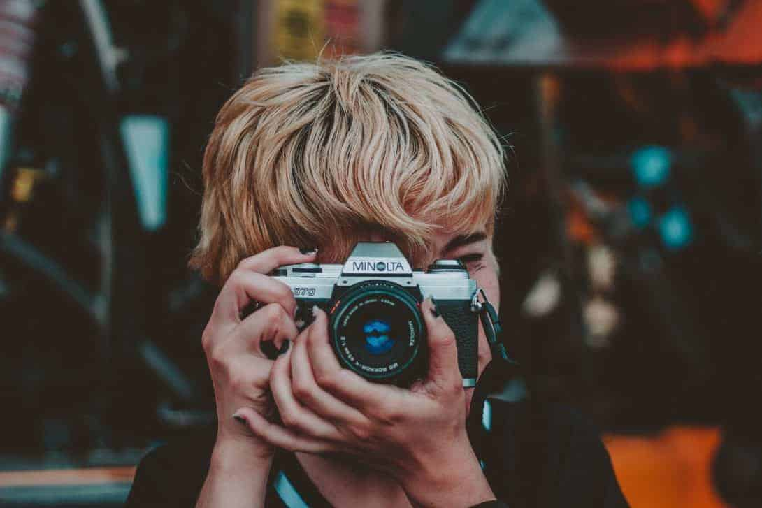 A Close-up of a woman taking a photograph with an old analogue camera