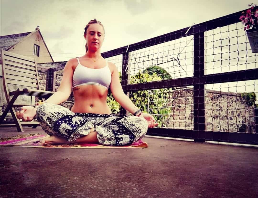 A girl meditating in a pair of elephant pants.