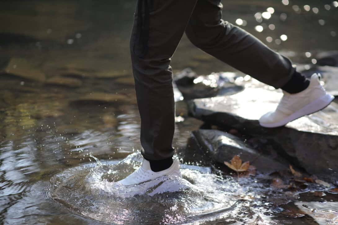 A man steps in a puddle to illustrate the waterproof aspect of Loom shoes