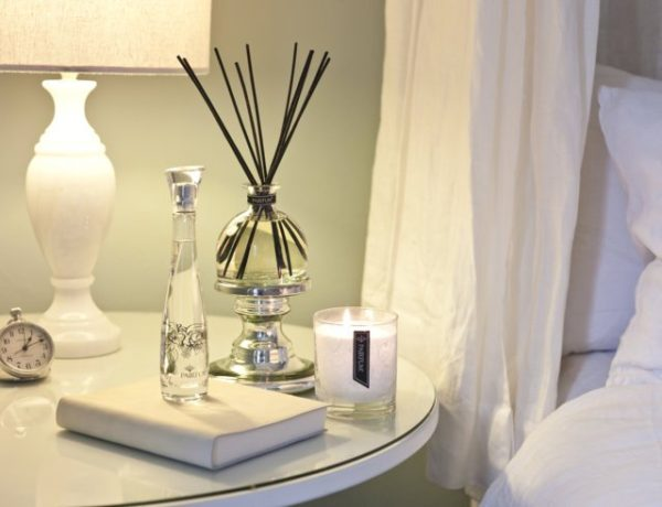 PAIRFUM luxury scented candle, natural reed diffuser and couture perfume room spray on the bedside table in a sixties style bedroom