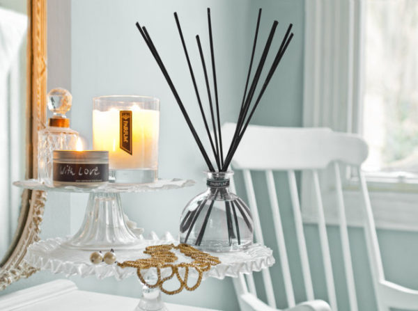 PAIRFUM luxury scented candle and natural reed diffuser on a cake stand in an English cottage