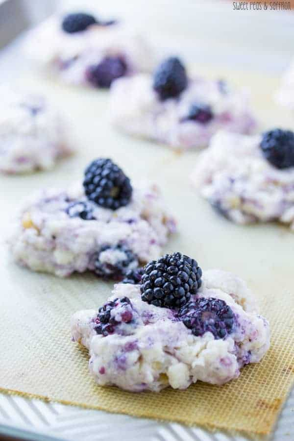 Close up shot of blackberry scones on silicone baking mat with fresh blackberries on top
