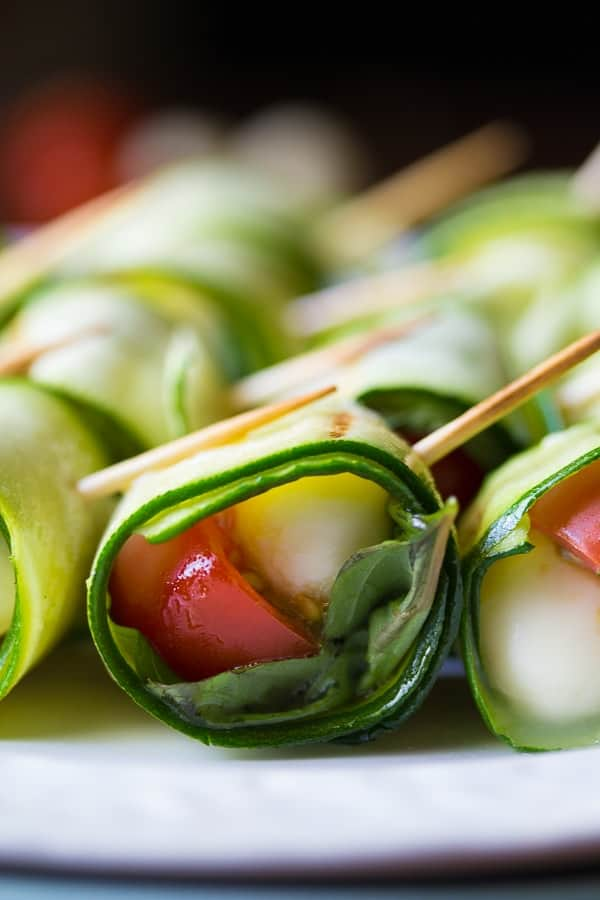 Side view of grilled caprese zucchini roll ups on a plate