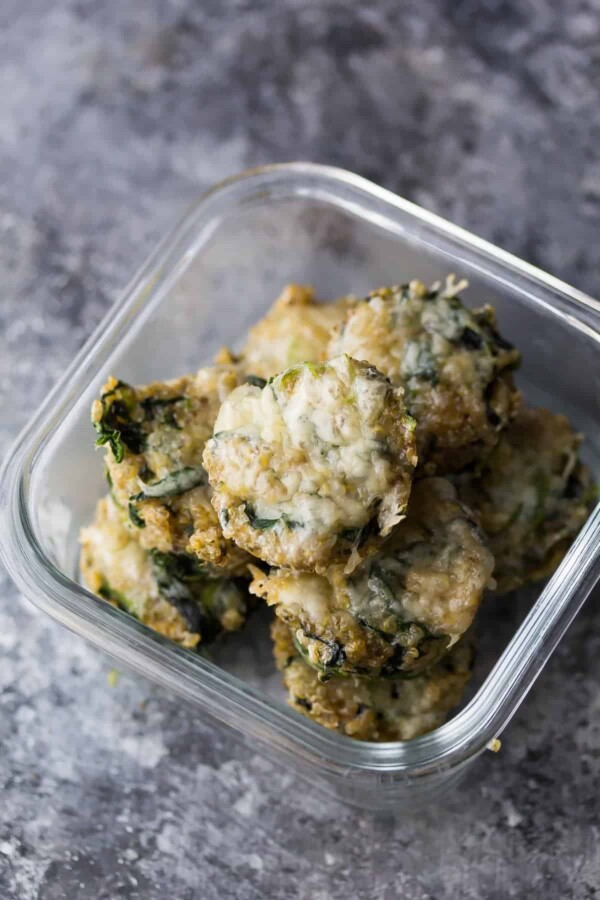 glass meal prep container with cheesy spinach quinoa cups on gray counter