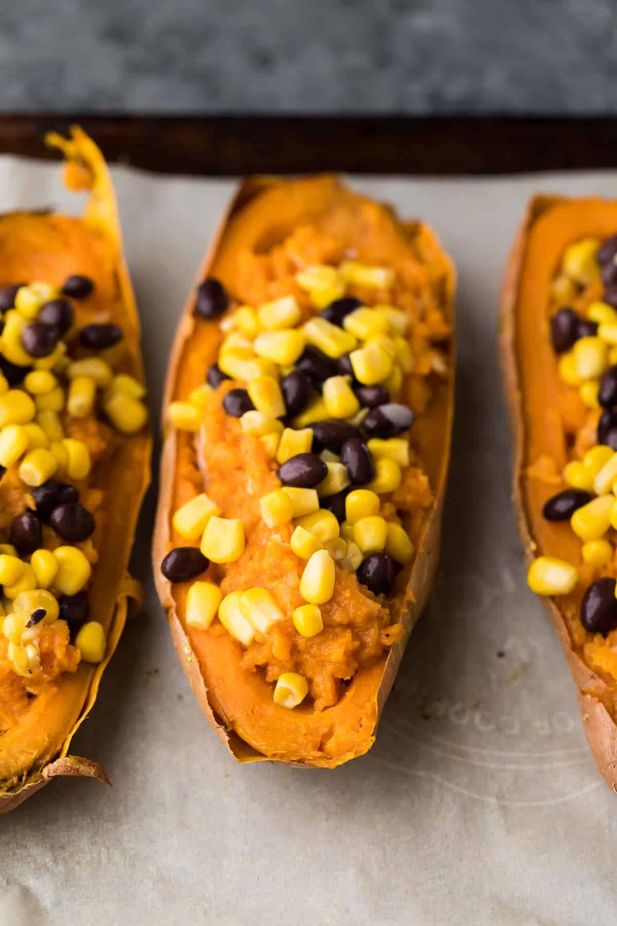Halved Sweet Potatoes lined up on a baking sheet with stuffing in the middle