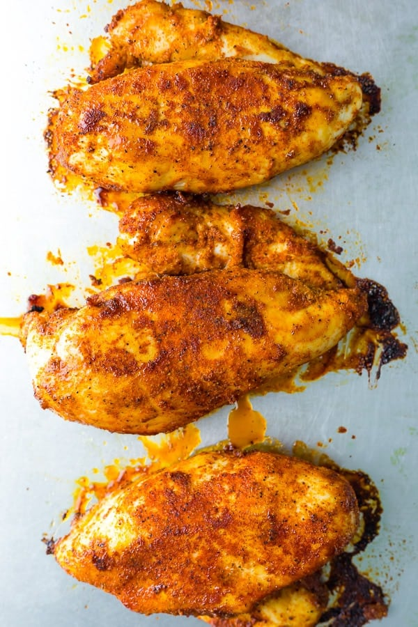 how to bake chicken breast- cooked chicken breasts lined up on baking sheet