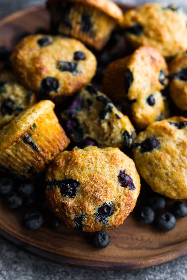 Pile of nine healthy blueberry muffins on a wood tray