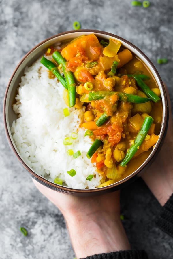 hands holding a bowl of chickpea curry cooked in the instant pot