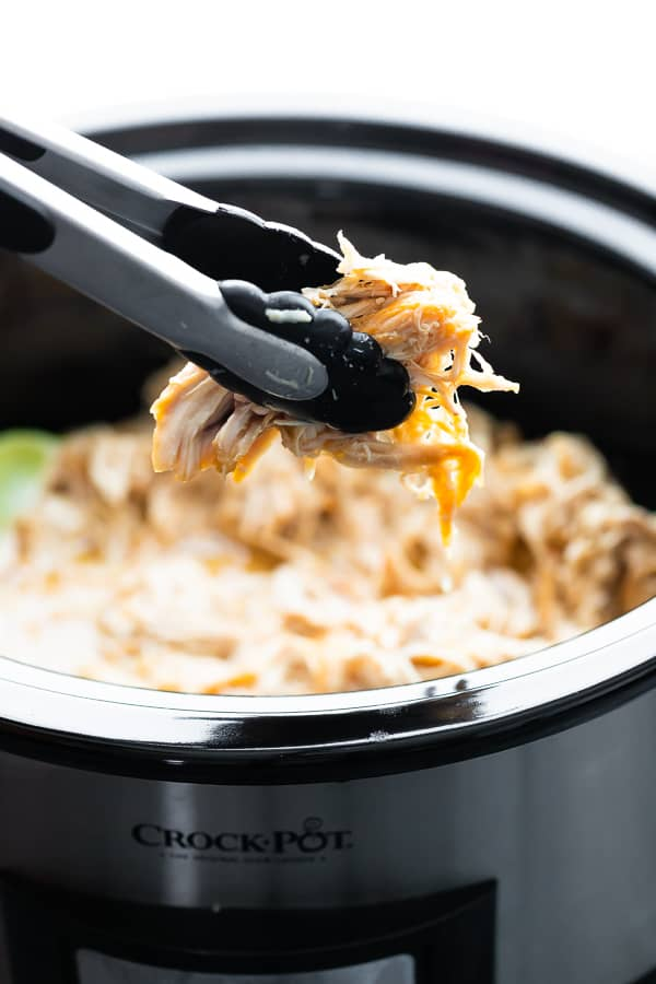 tongs picking up Slow Cooker Honey Lime Chicken