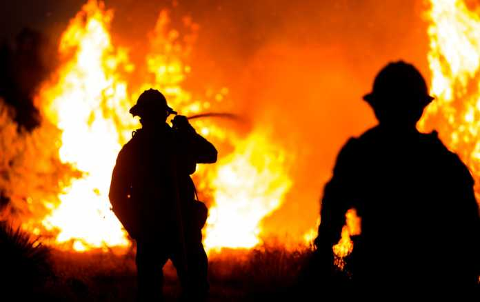 Firefighters stare into a fire.