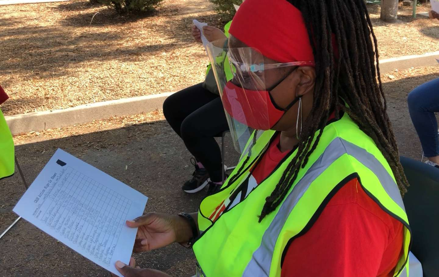 A CASE canvasser in PPE reviews a list of names.