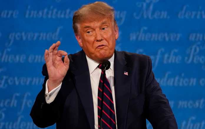 Trump speaks with his right hand up, gesturing.