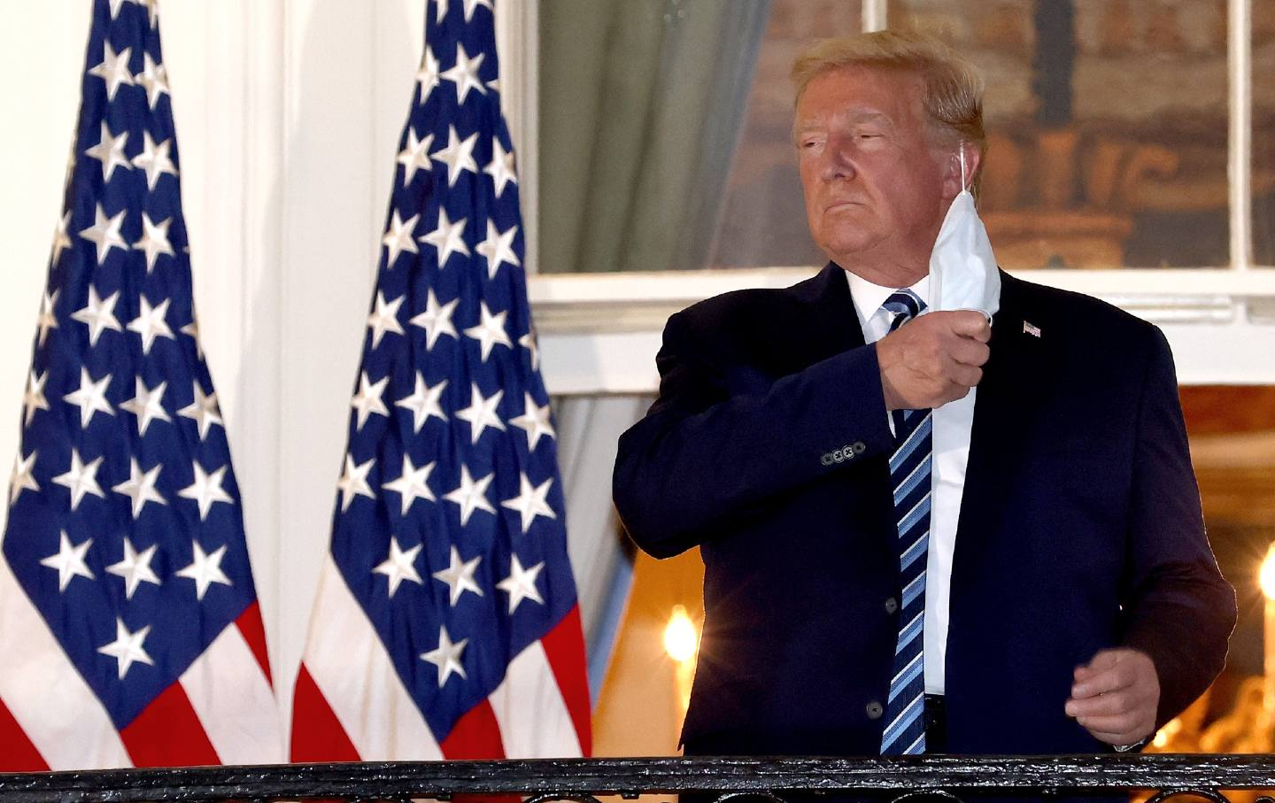 Standing on the White House balcony, Donald Trump removes his mask.