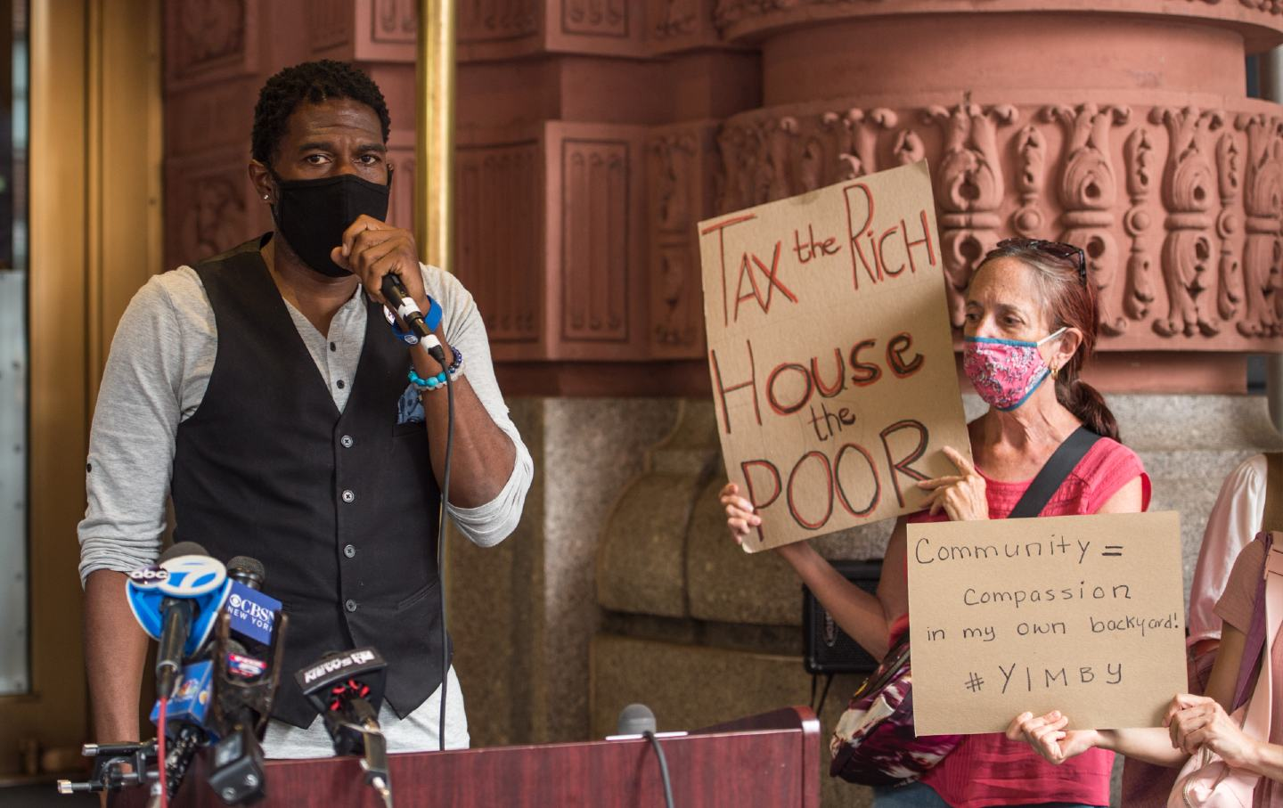 Jumaane Williams stands on the left while an unnamed protester stands on the right, holding a sign that reads