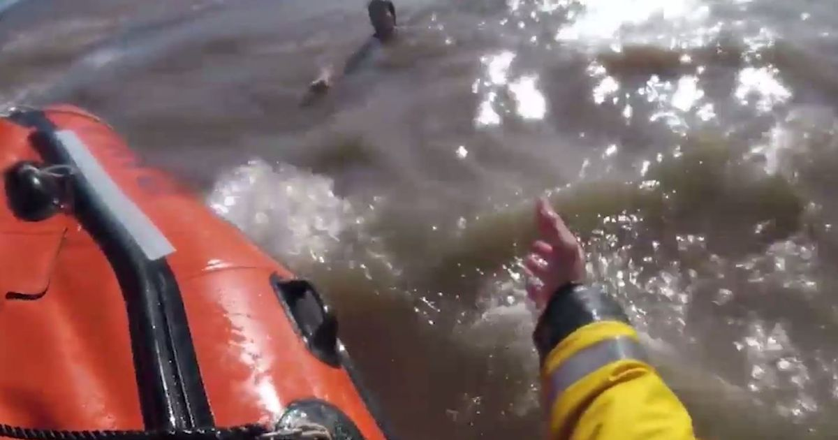 Dramatic moment stranded swimmers' lives saved by lifeboat