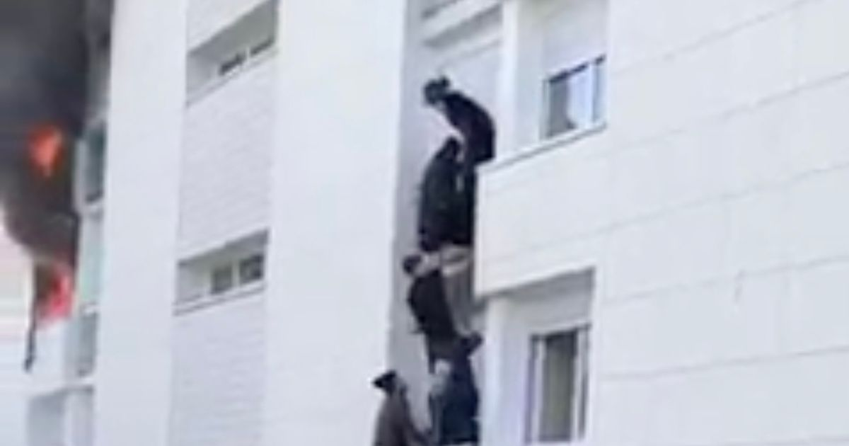 Baby survives after being thrown out of a third-storey window to escape fire