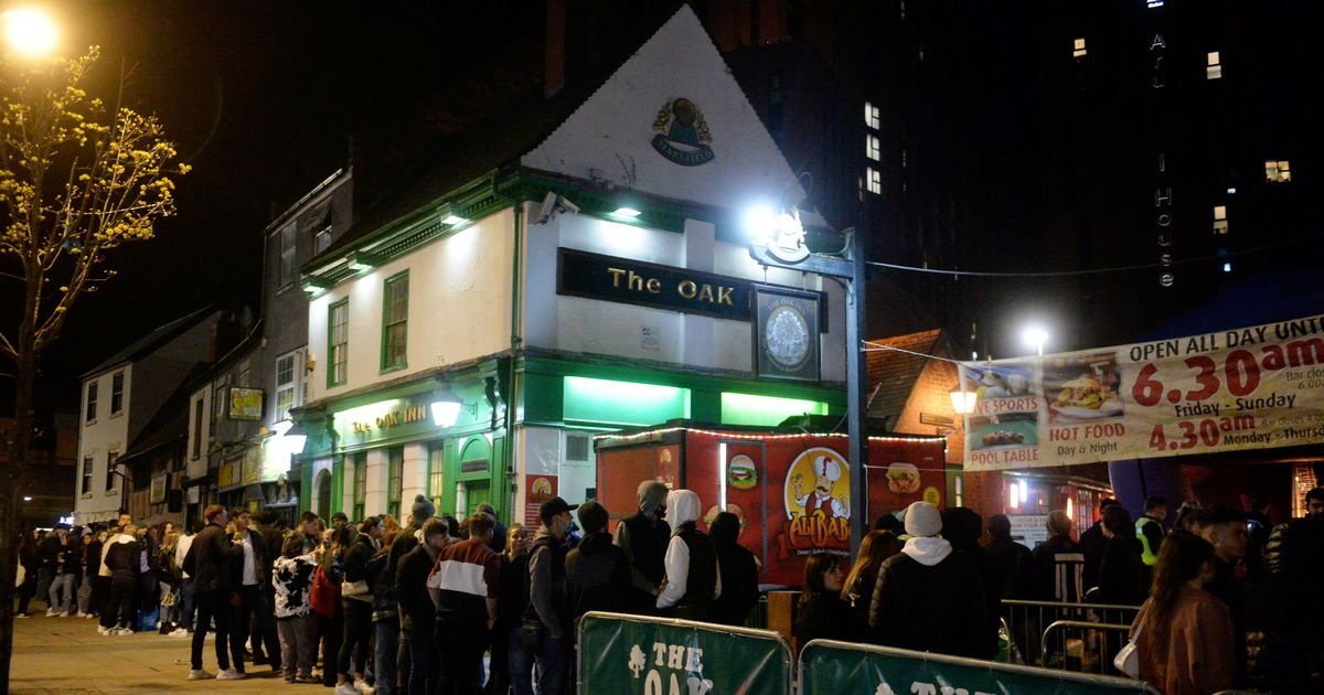 People queue outside pubs in England for an outside pint at midnight