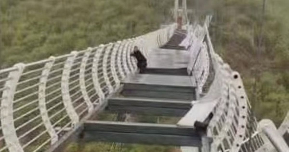 Terror after man left dangling from 100m-high glass bridge after floor collapsed
