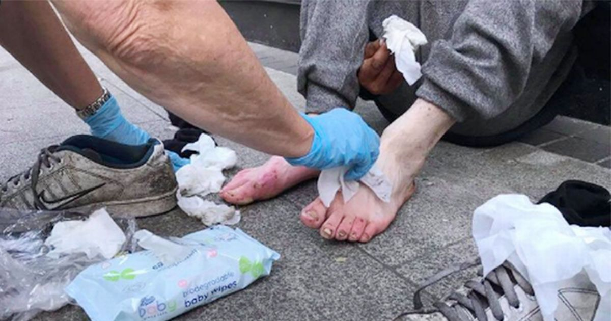 Heartbreaking photo shows strangers caring for injured homeless man in street