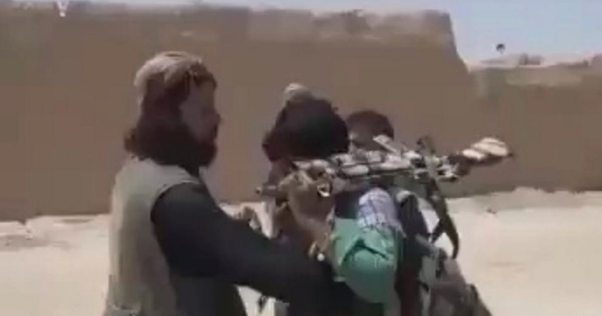 Afghan troops seen shaking hands with Taliban as they give them their weapons