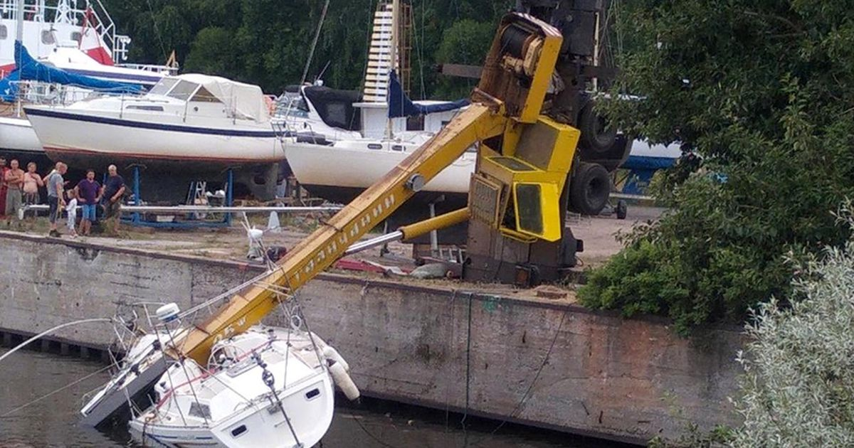 Crane lowering super yacht into water topples over and crashes onto sinking boat