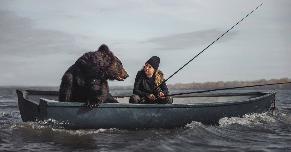 Fearless woman goes fishing with giant brown bear in a boat to prove he is safe