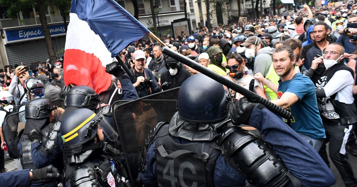 CRS riot police charge demonstrators on the sidelines of a demonstration as part of a national day of protest against French legislation making a Covid-19 health pass compulsory to visit a cafe, board a plane or travel on an inter-city train, in Paris on July 31