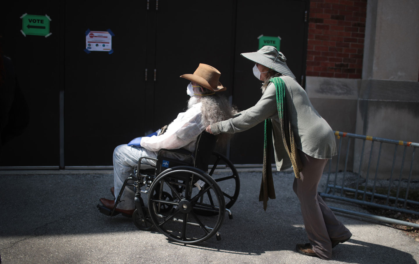 A person in wheelchair, being pushed by another person, waiting to cast their vote in the Wisconsin primary election