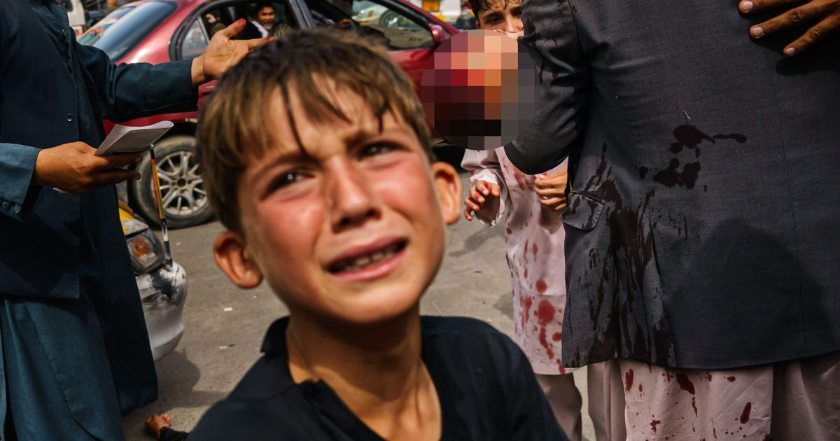 A small boy sobs as a man carries a bloodied child behind him in Kabul, after Taliban fighters used guns, whips and sticks to control the desperate crowds outside the airport