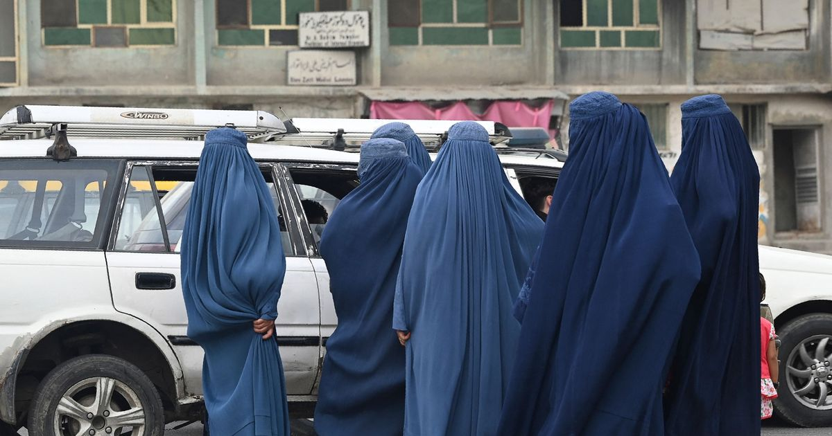 Women wearing a burqa wait to board into a local taxi in Kabul on July 31
