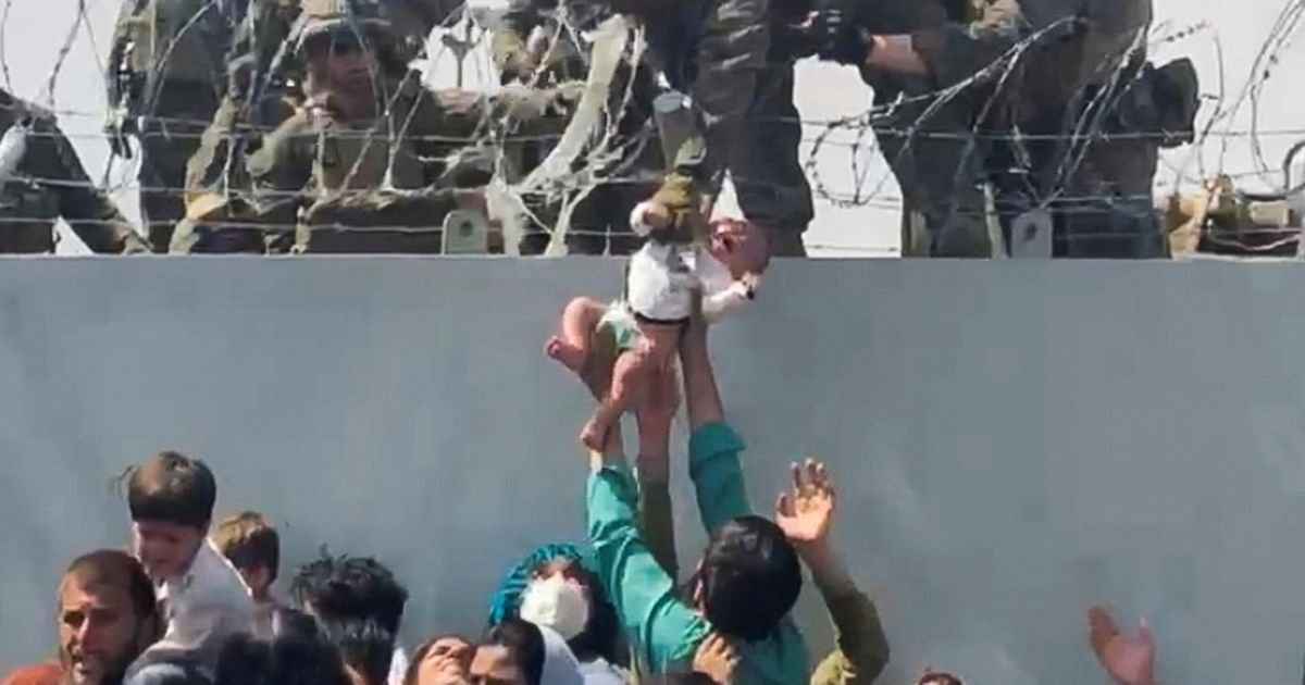 Crying Afghan baby lifted over barbed wire is safe and reunited with dad, say US Marines