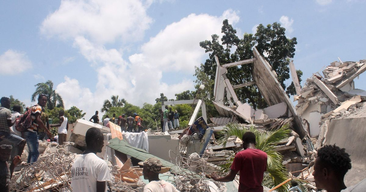 People search through the rubble of what used to be the Manguier Hotel after an earthquake hit in Haiti