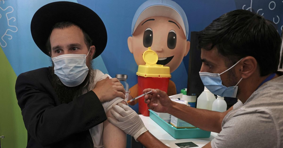 An Israeli health worker administers a dose of the Pfizer-BioNtech COVID-19 vaccine at the new vaccination centre for Clalit Health Services in Jerusalem