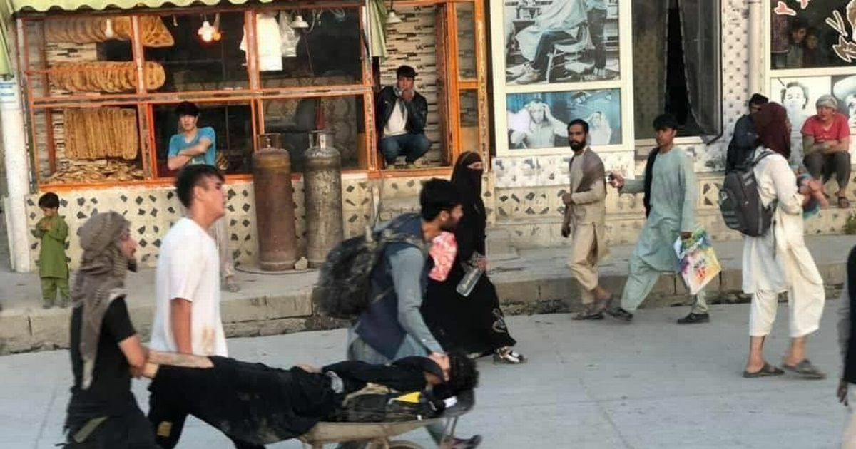 People rush casualties away from the explosion site outside Kabul
