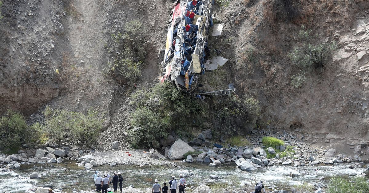 Rescue workers check a bus after it crashed
