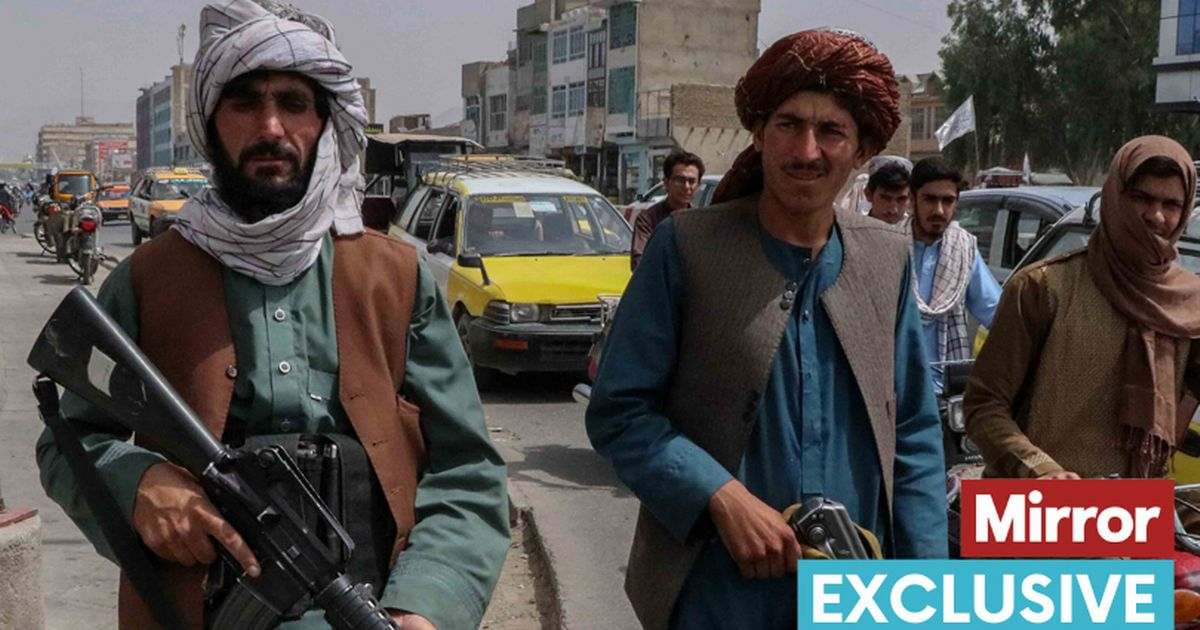 Taliban fighters stand guard at a checkpoint in Kandahar