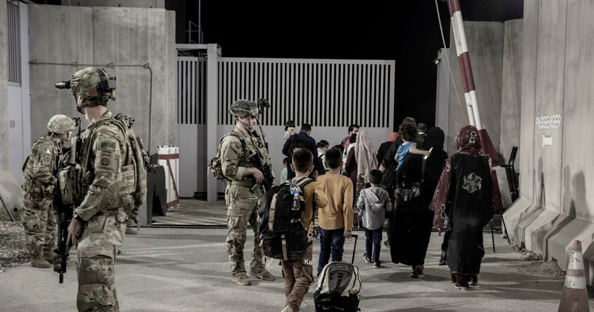 U.S. soldiers with the 82nd Airborne Division escort evacuees to buses for onward movement during an evacuation at Hamid Karzai International Airport in Kabul, Afghanistan