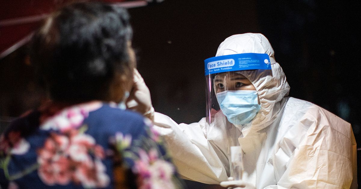 A medical worker takes samples during a mass Covid-19 test in a residential block on August 6, 2021 in Wuhan, Hubei Province, China