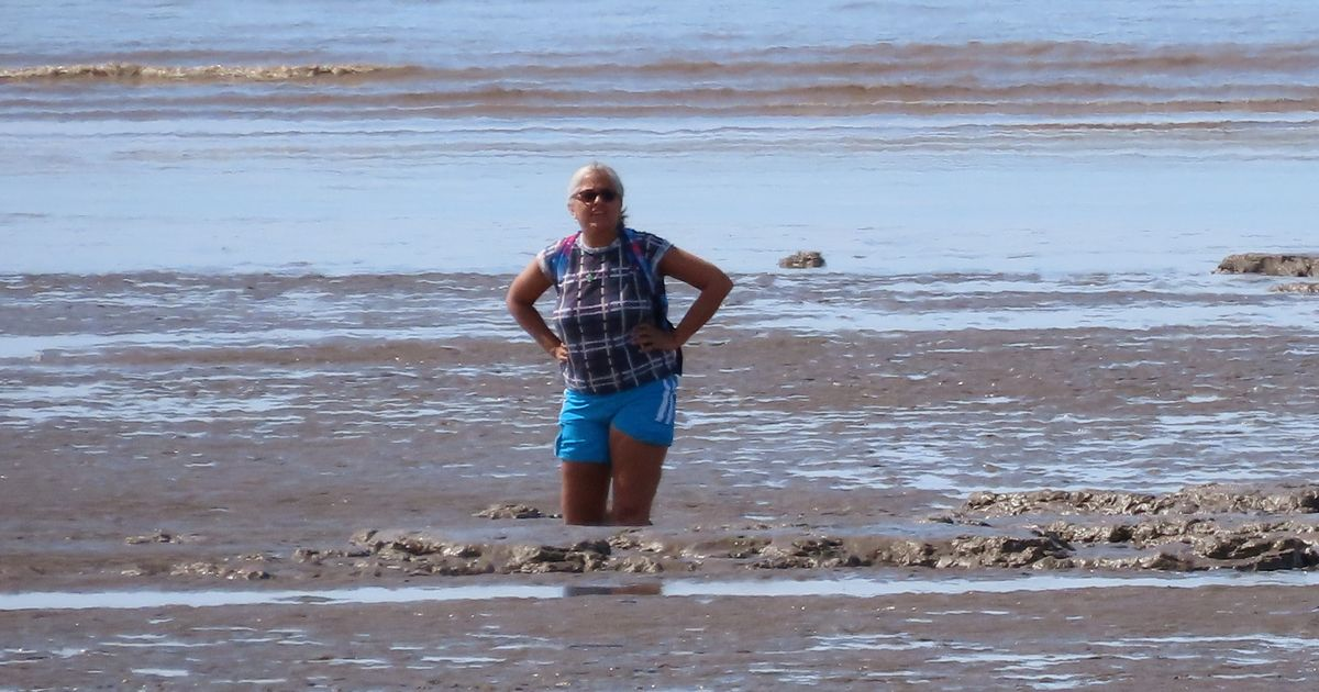 Woman rescued from a beach after getting swallowed up by mud