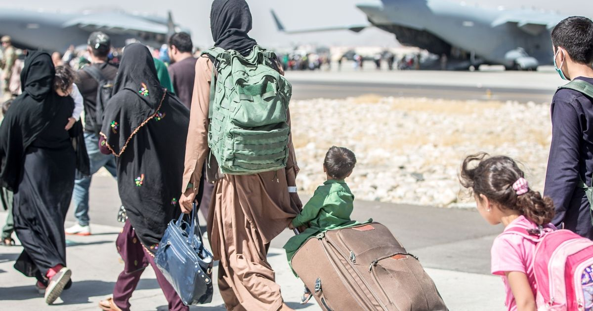 A handout photo made available by the US Marine Corps via DVIDS showing a child looks at the aircraft as he is strolled towards his flight during an evacuation at Hamid Karzai International Airport, Kabul, Afghanistan
