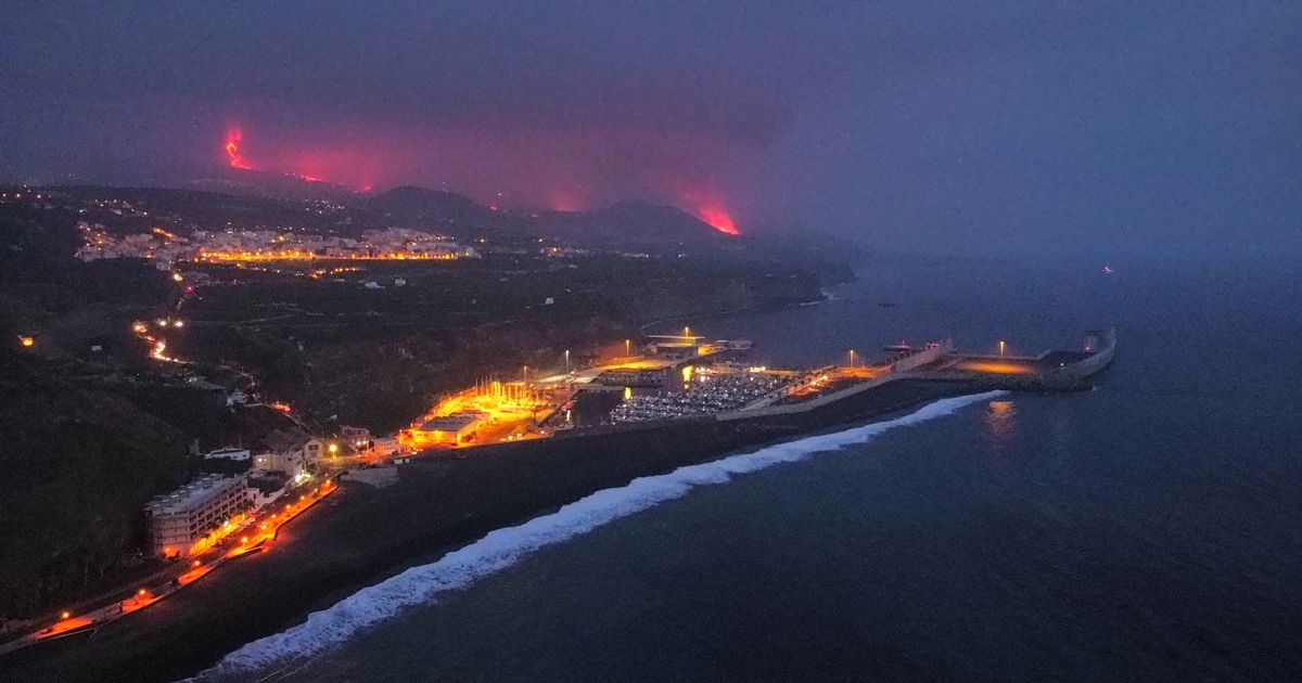 Lava is seen and smoke rises following the eruption of a volcano